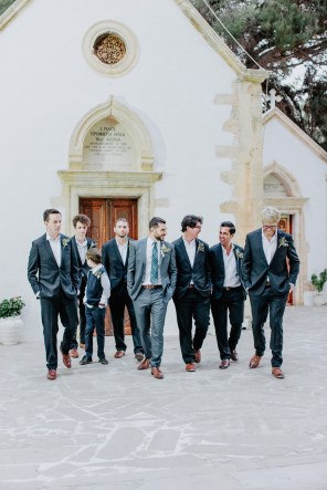 Stylish groom with group of his groomsmen posing for the wedding photographer on a summer wedding in Chania, Crete.