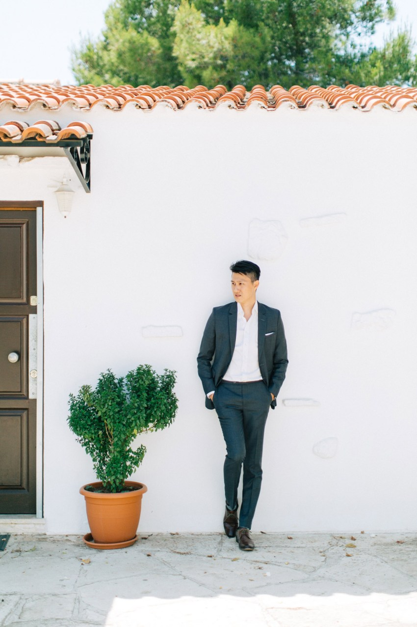 Young elegant man wearing formal suit and is posing for his elopemement portraits for professional photographer team in Crete island, Greece. Colorful garden and park backdrop adds to the happy and vibrant feel of this session.