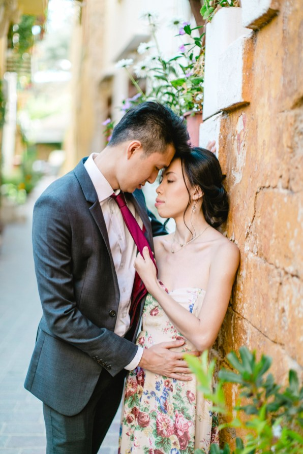 Young Asian couple in love during their engagement portrait session in old town of Chania, Crete. They're hugging and posing for photos with the backdrop of Greek architecture.