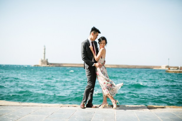 Young Asian couple in love during their engagement portrait session in the harbour and port of Chania, Crete. They're having fun and posing for photos with the backdrop of sea.