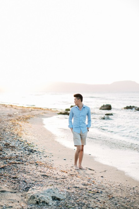 Young good looking man wearing summer clothing is posing for professional photographer team during his beach destination photoshoot on the secluded shores of Rethymno town, Crete, Greece.