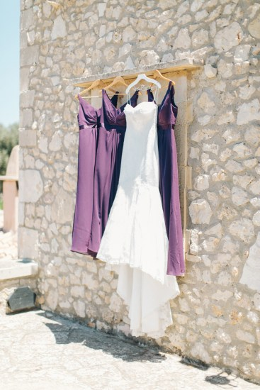 Bridal gown and bridesmaids' dresses in white and purple photographed in Agreco farm during destination wedding in Crete.