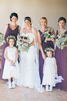Elegant bride and her bridesmaids posing for fine art wedding photographer on a June destination wedding day in Agreco Farm in Crete.