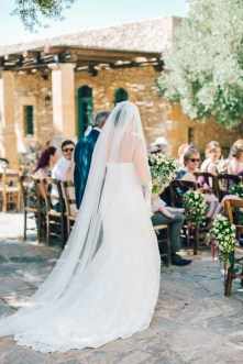 Candid image of elegant bride walking down the aisle into the wedding ceremony on a destination wedding day in Agreco Farm in Crete.