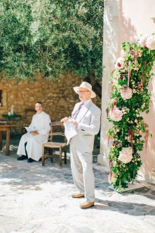 Candid image of an elegant wedding minister giving a speech on a destination wedding day in Agreco Farm in Crete, Greece, captured by their wedding photographer.