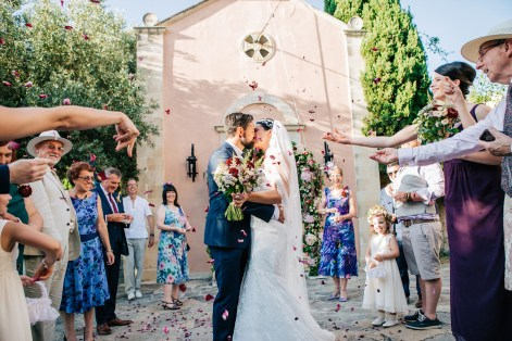 Candid image of bride and groom after their wedding ceremony at Agreco Farm in Crete, Greece. Guests are having fun and throwing rose petals for the newlyweds.