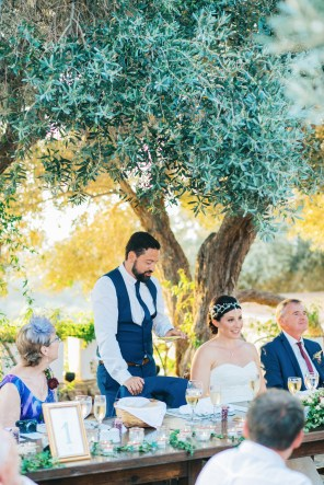 Candid image of bride and groom having time of their life during wedding speeches at dinner in Agreco Farm in Crete.