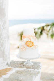 Wedding cake with a background of Mykonos windmill stones.