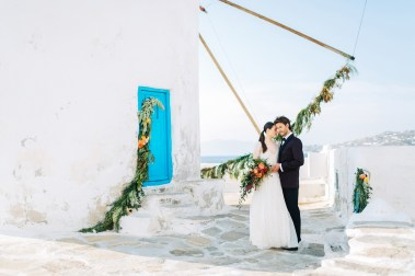 Stylish bride and groom on their destination wedding in Mykonos, posing under the windmills.