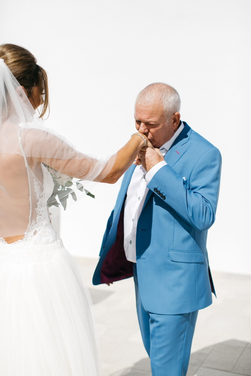 Bride's first look with her father at luxury white wedding in Santorini island, Greece.