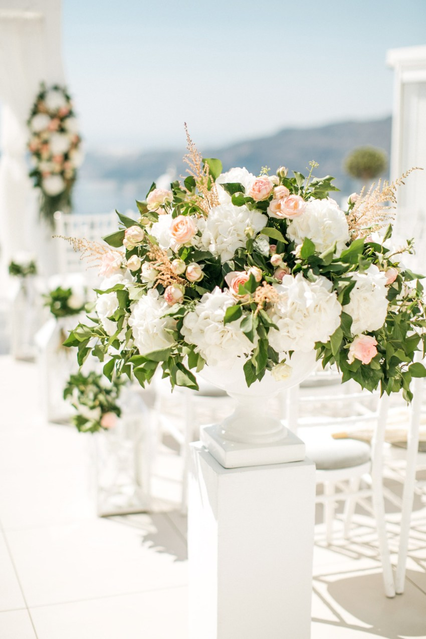Wedding ceremony decoration and setup for luxury white wedding in Santorini island, Greece.