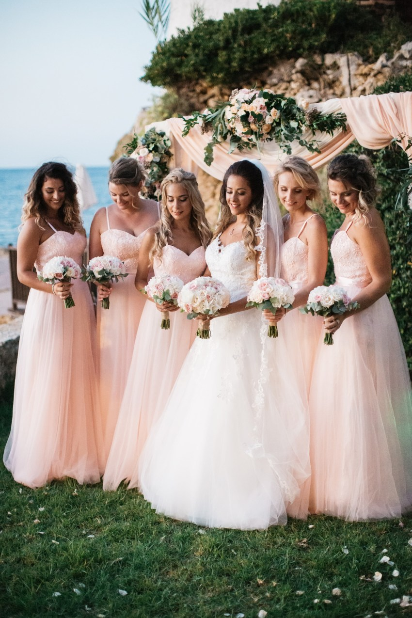 Bride with her bridesmaids holding matching wedding flowers in Chania Crete Greece.