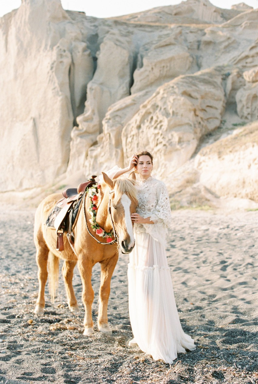 Beautiful bride wearing designer wedding dress holding a horse at a volcanic beach wedding inspiration session in Santorini Greece.