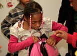A young girl tries on a new coat provided by the Knights of Columbus at the HALO homeless shelter in Racine, Wis.