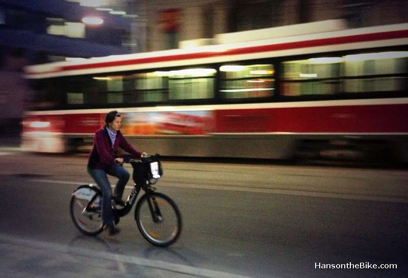woman cycling next to street car in Toronto