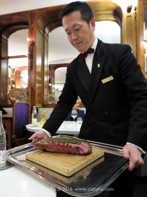 侍者端來將要片切上桌的主菜伊比利豬排展示給客人看