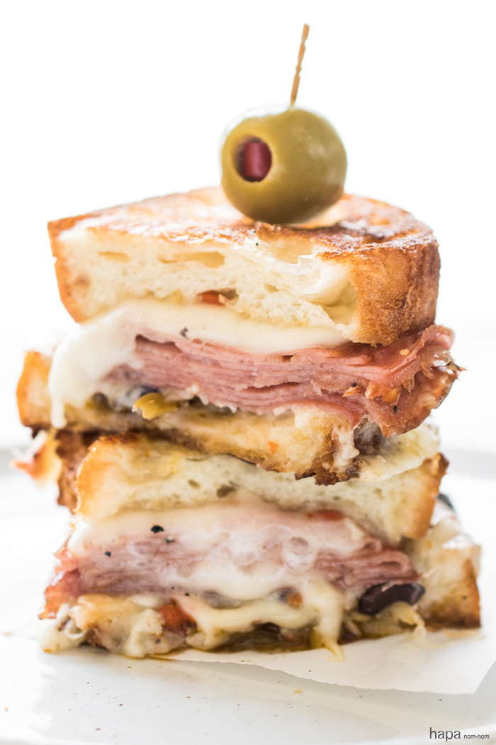 A Hot Muffuletta Sandwich dripping with cheese and packed with punch!