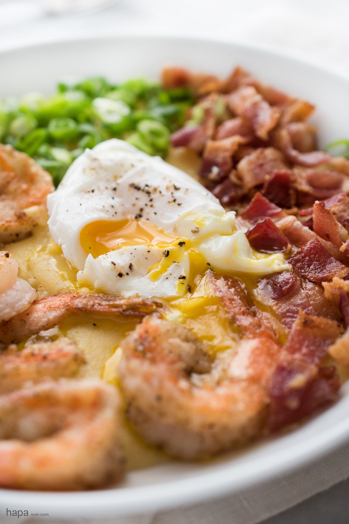 This is a dish that makes a great meal anytime of day! Wether you want a big breakfast, a hearty dinner, or any meal in between; lightly crispy salt & pepper shrimp over cheesy grits, garnished with crispy bacon, scallions, and topped with a creamy poached egg is a dish that will keep you going!