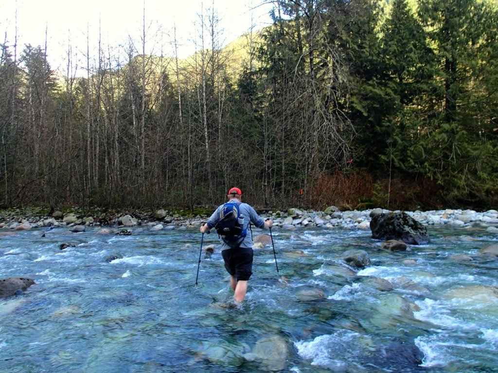 A hiker crossing Lynn Creek on the Big Cedar and Kennedy Falls hike