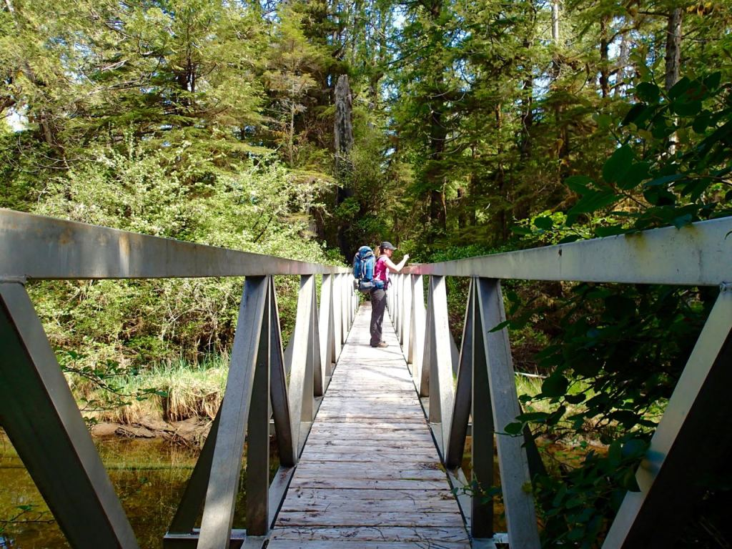 Hikers crossing the bridge over the Kutcous River on the Wild Side Trail near Tofino, BC.