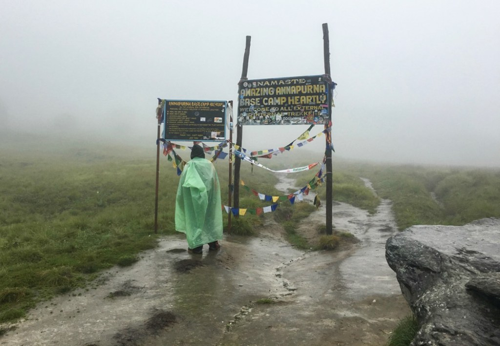 Nepali guide wearing a plastic sheet as a rain cover at Annapurna Base Camp. What to pack for the Annapurna Base Camp Trek in Nepal.