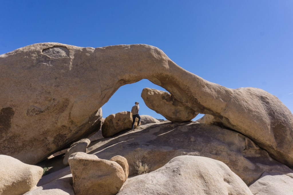 The natural rock arch at Arch Rock in Joshua Tree National Park, one of 15 awesome things to do in Joshua Tree. Add visiting Arch Rock to your Joshua Tree bucketlist.