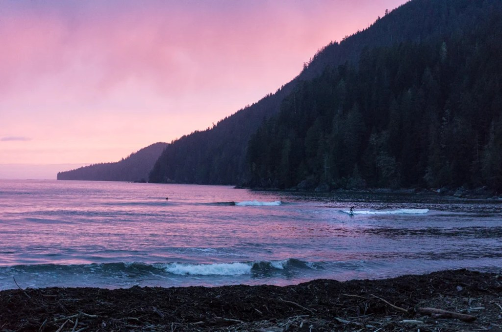 A surfer at sunset at the Pacheedaht Campground in Port Renfrew. It makes a great place to camp on a road trip on the Pacific Marine Circle Route on Vancouver Island.
