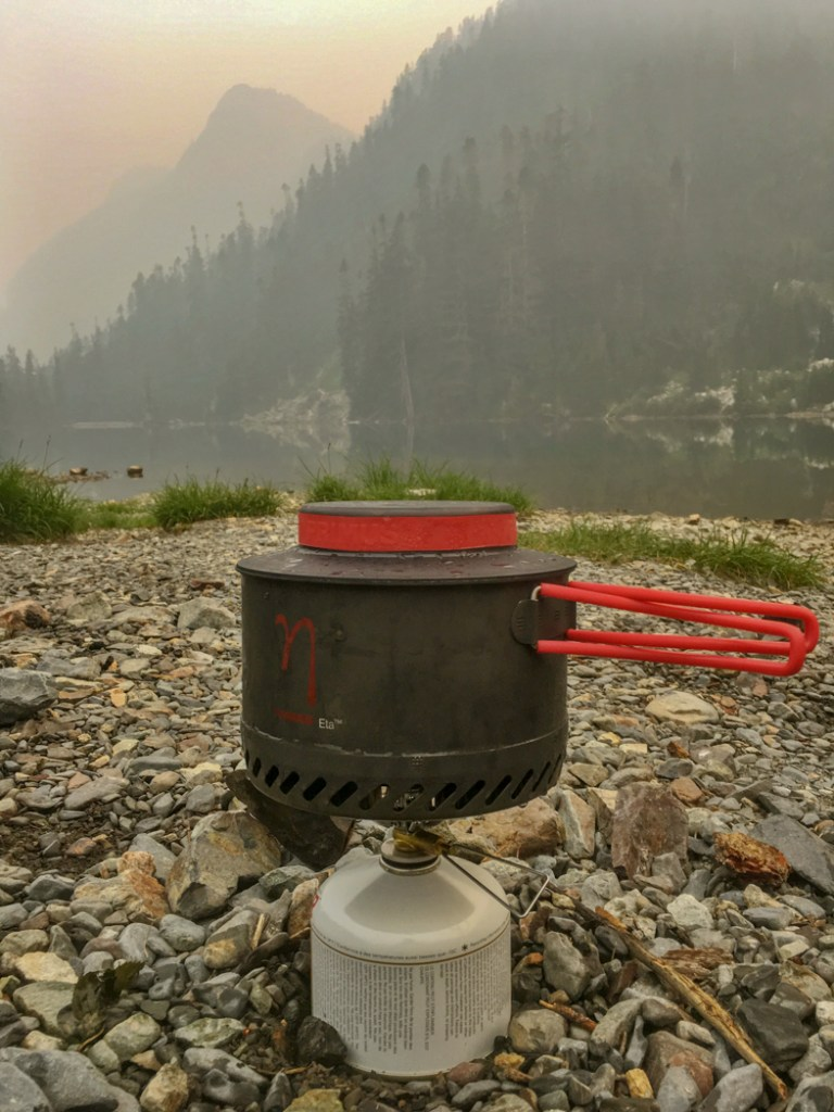 Camp stove at a foggy lake. How to choose backpacking meals.