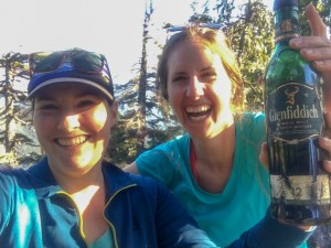 Two hikers with a bottle of whiskey found on a mountain top. Learn how to find hidden whiskey caches in the mountains of Vancouver in the book The Glorious Mountains of Vancouver's North Shore.