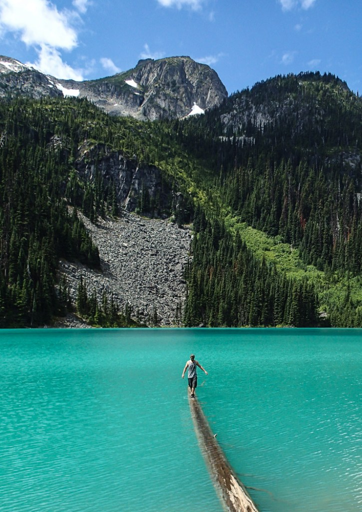 A hiker balances on a log at Joffre Lakes near Vancouver