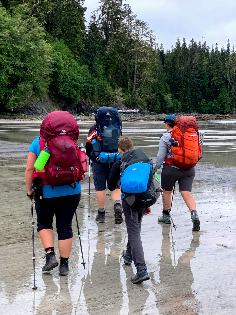 Hikers walking on the beach at Pachena Bay to start the first West Coast Trail section
