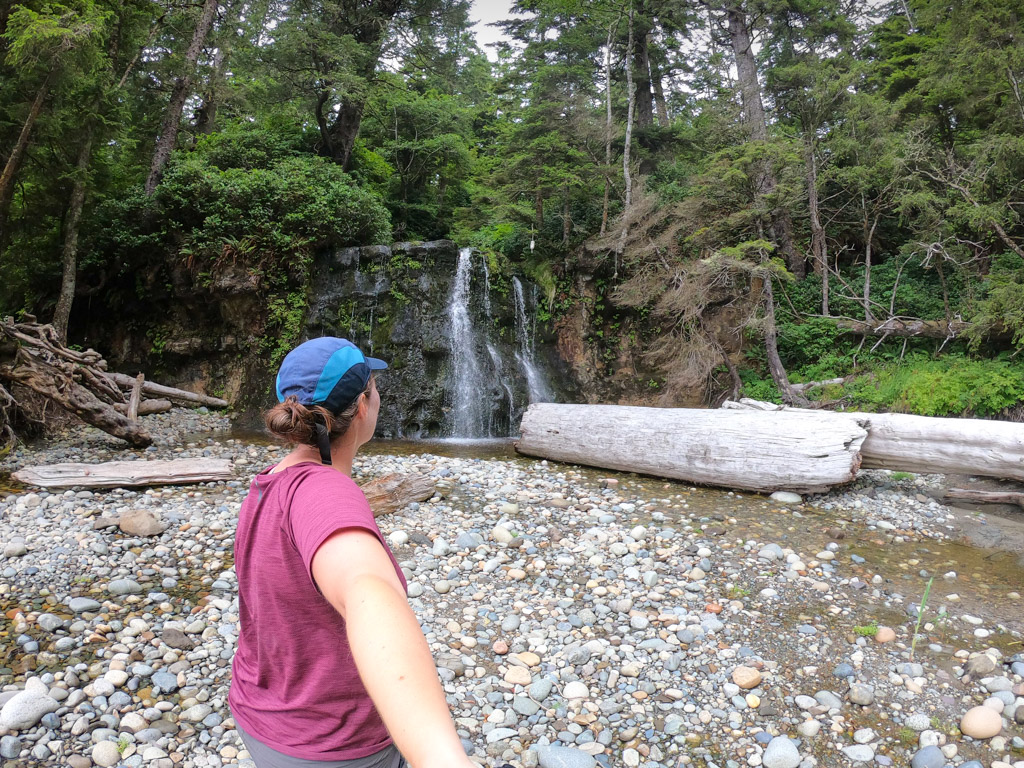 A hiker in front of a waterfall on the West Coast Trail