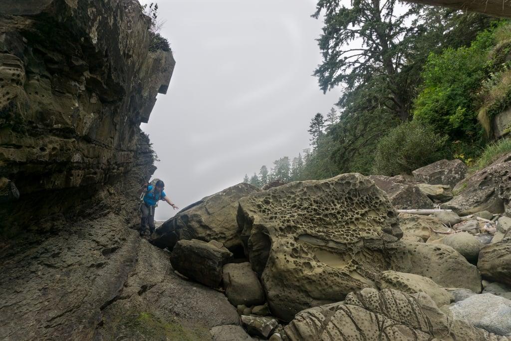 A hiker scrambles over rocks at a headland on the West Coast Trail