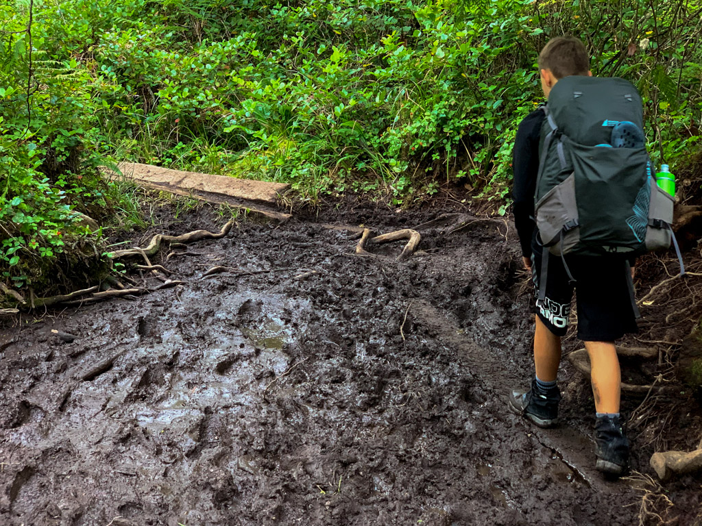 A hiker navigates through a mud bog on the West Coast Trail