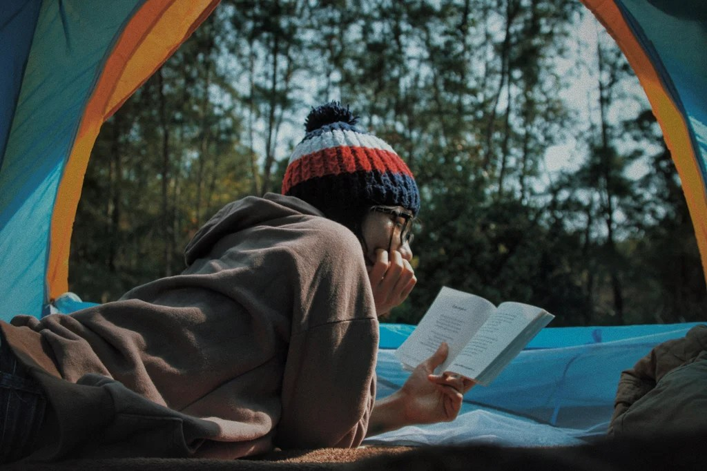 A woman reading a book in a tent. Get recommendations for the best women's adventure books from this list