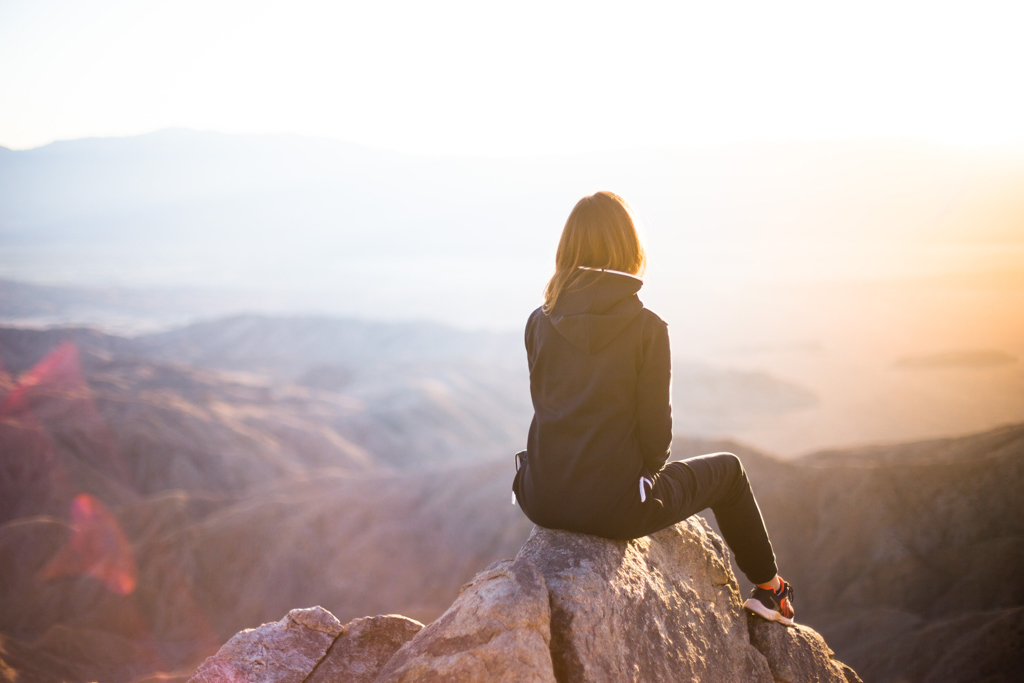 A woman sitting on the peak of a mountain