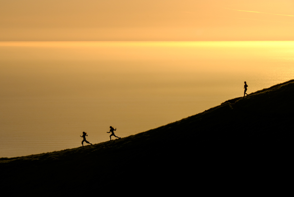The silhouettes of three women as they run down a hill at sunset. Get this list of women's adventure films about running.