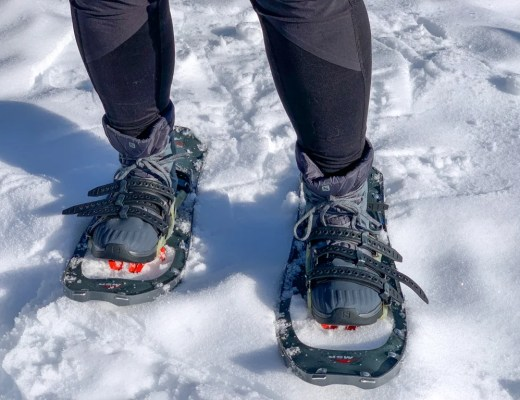 Close up of a a person wearing insulated hiking boots with snowshoes. The best boots for snowshoeing