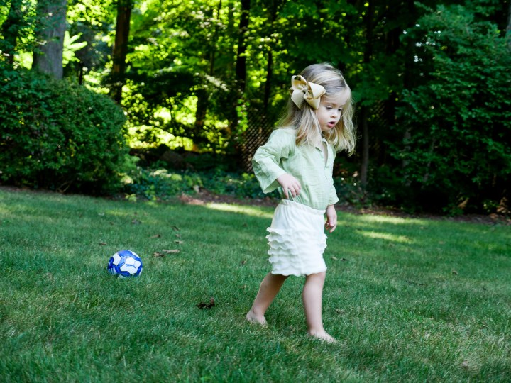 Marlowe Martino from the Happily Eva After Blog wearing a green tunic and ruffled white shorts and bow, walking on the grass at her home in Connecticut with a blue and white soccer ball