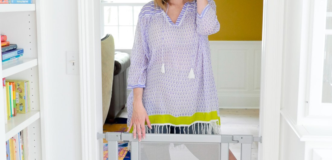 Eva Amurri Martino of lifestye blog Happily Eva After wearing a roberta roller rabbit tunic and maternity denim shorts, installing a munchkin safety gate in her new connecticut home