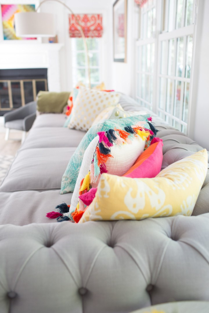multicolored pillows on a grey couch in the family room of Eva Amurri Martino of lifestyle blog Happily Eva After