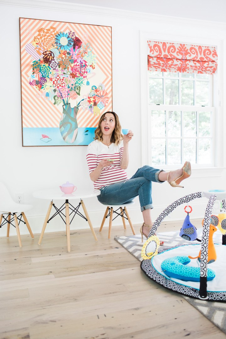 Eva Amurri Martin of lifestyle blog Happily Eva After drinking tea from her daughter's tea set and perching on a tiny white midcentury modern playroom furniture set with the jonathan adler crafter by fisher price collection sensory gym in the foreground