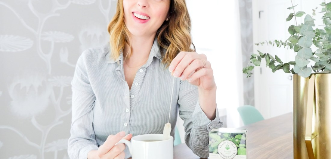 Eva Amurri Martino of lifestyle blog Happily Eva After sits at her dining room table in connecticut wearing a blue and white striped maternity top and dunking a tea bag in to a white mug