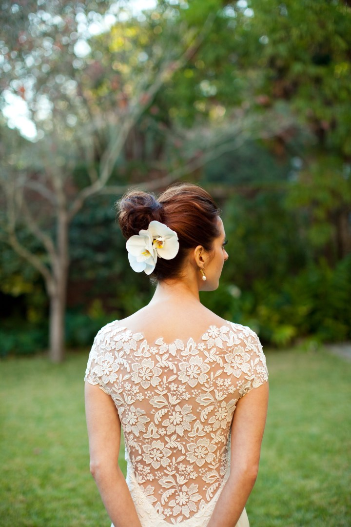 The back detail of Eva Amurri Martino's Lela Rose wedding dress, worn with a high bun hairstyle and two white orchids pinned in the back
