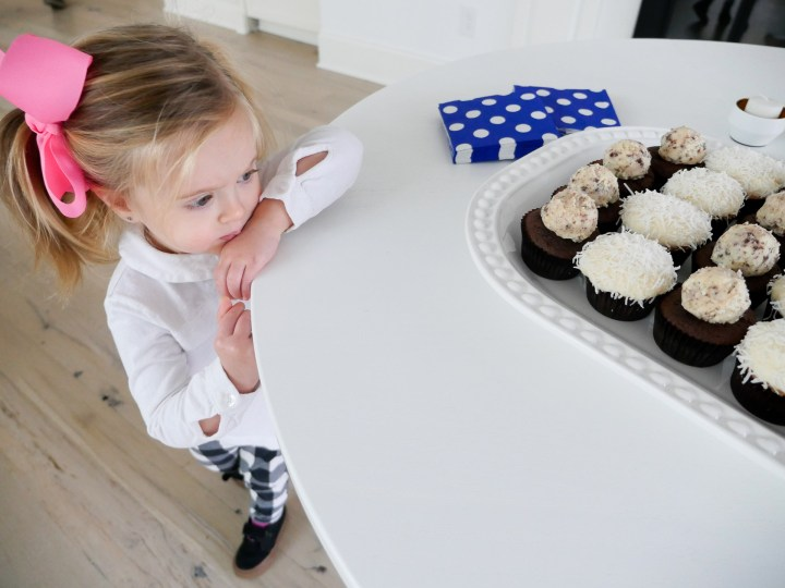 Marlowe Martino wearing a white top and pink bow, eyeing a tray of cupcakes