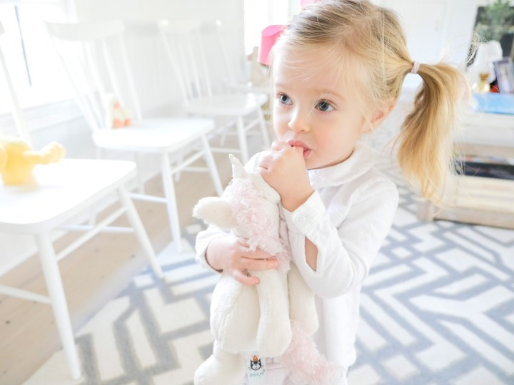 Marlowe Martino, wearing a white top and bright pink bow, clutching a stuffed unicorn