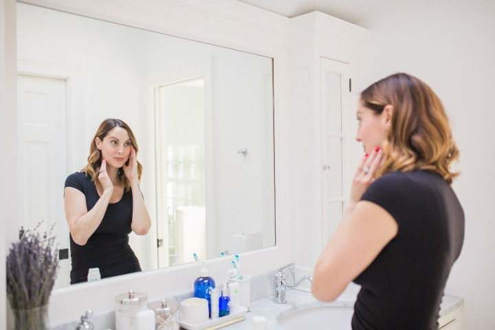 Eva Amurri Martino of lifestyle and motherhood blog Happily Eva After applying face cream in the master bathroom of her connecticut home