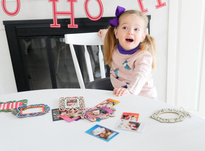 Marlowe Martino crafts Holiday photo ornaments at the kitchen table using Instax Mini 70 instant film