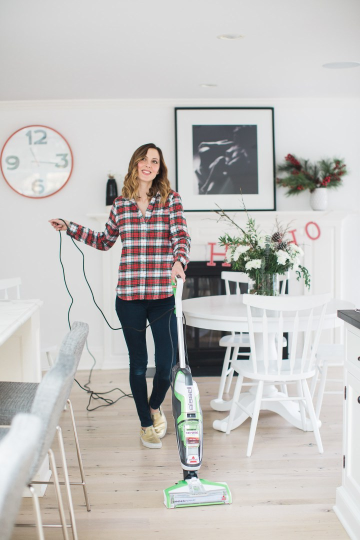 Eva Amurri Martino vacuums in her kitchen wearing a plain flannel shirt and blue jeans