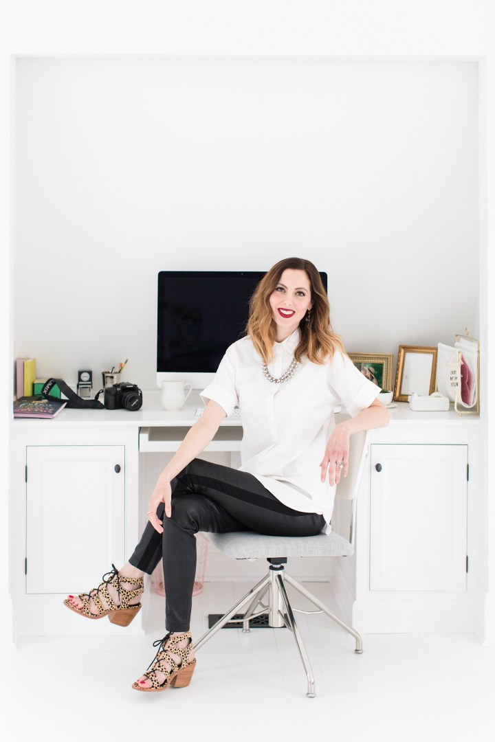Eva Amurri Martino sits at her desk for blog Happily Eva After, wearing a white button down shirt, leather leggings, leopard print sandals, and red lipstick